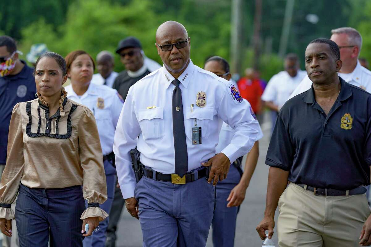 Prince George's County Executive Angela Alsobrooks and Police Chief Malik Aziz, center, walk in an area where a woman was killed in a drive-by shooting May 26 in Capitol Heights, Md.