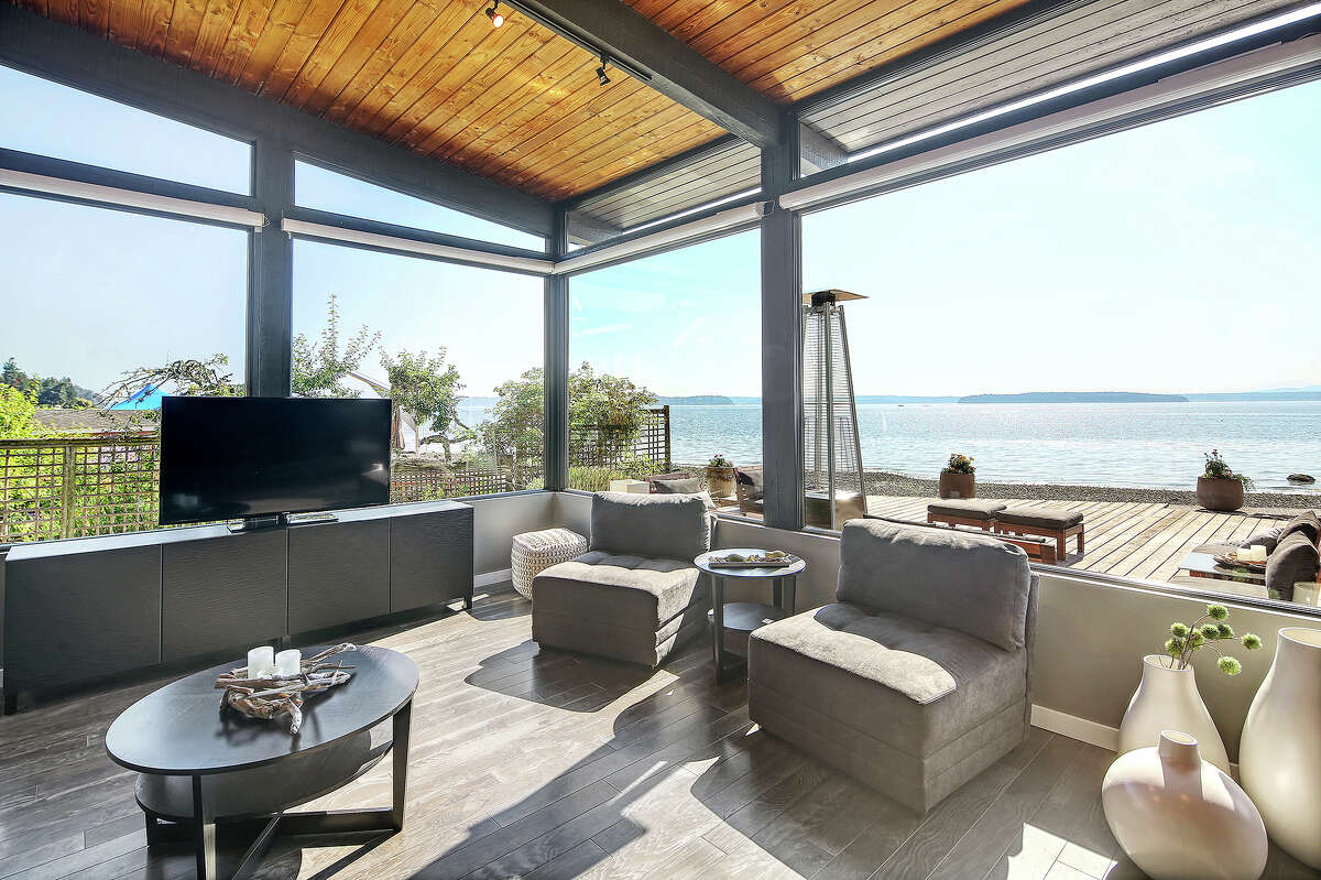 The living room features walls of glass that allow the beach and water to become part of the interior.