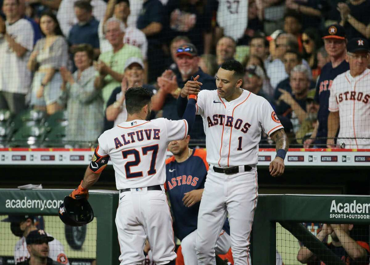 Jose Altuve celebrates his first-inning home run with teammate Carlos Correa. Altuve was just getting started on the 10th anniversary of his major league debut, homering twice during the Astros' victory over Cleveland.