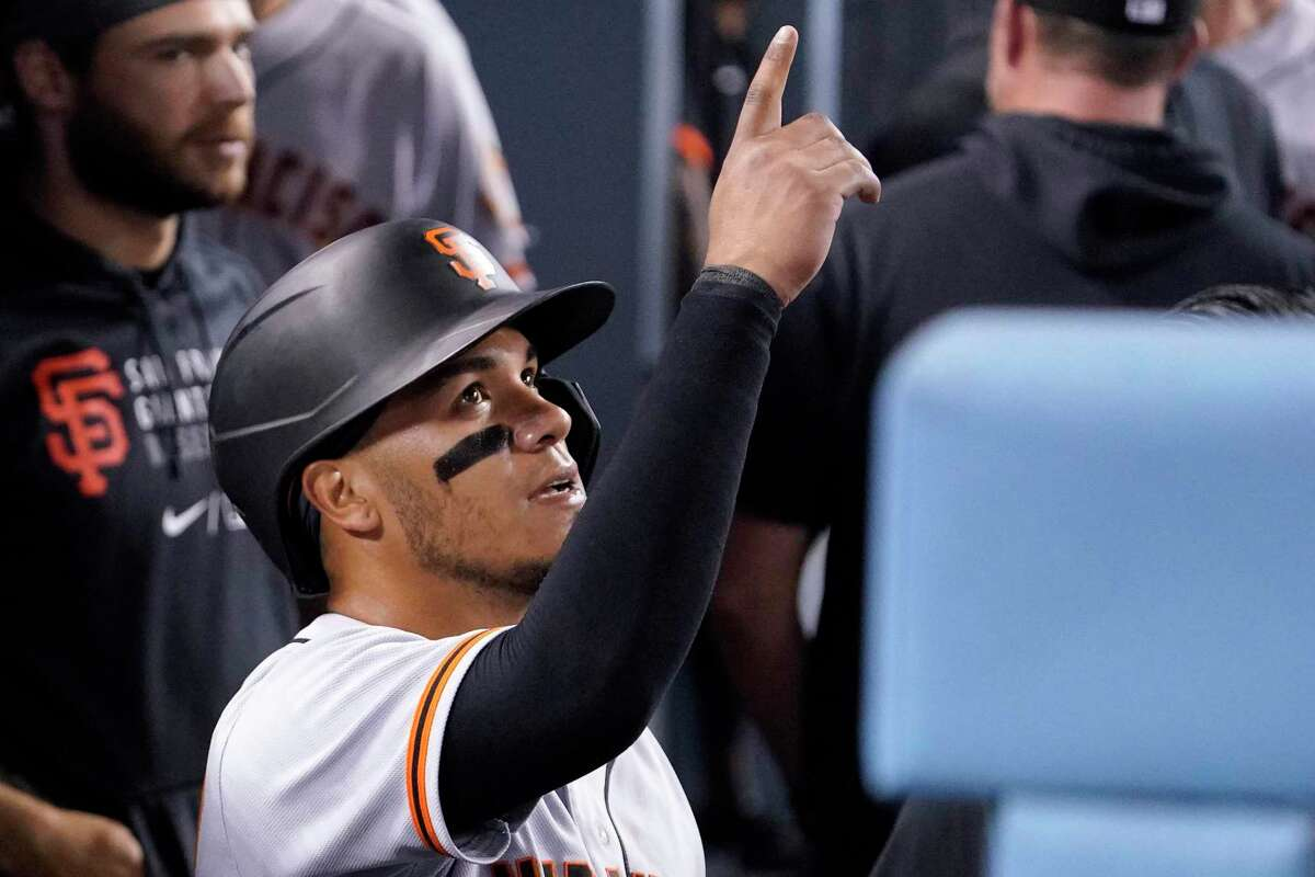 San Francisco Giants' Thairo Estrada gestures in the dugout after scoring on a double by Austin Slater during the seventh inning of a baseball game against the Los Angeles Dodgers Monday, July 19, 2021, in Los Angeles. (AP Photo/Mark J. Terrill)