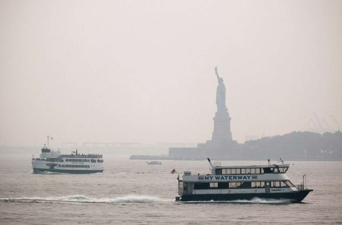 The Statue of Liberty sits behind a cloud of haze in New York City on Tuesday, with wildfire smoke from the West arriving in the region.