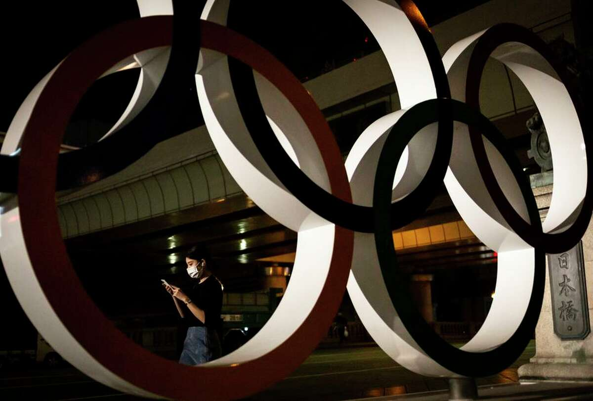 A woman in a face mask walks past a statue of the Olympic rings in Tokyo, where the Games will be held without fans.