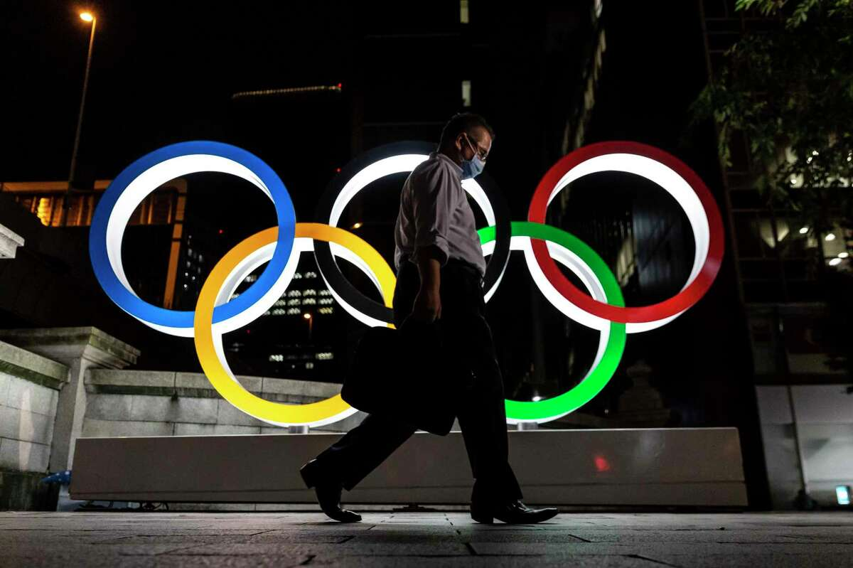 TOKYO, JAPAN - JULY 20: A man wearing a face mask walks past the Olympic Rings on July 20, 2021 in Tokyo, Japan. With the Olympics now just a few days away, Tokyo is bracing itself for a Games without foreign fans or local attendance and a population enduring its fourth state of emergency amid the continuing global coronavirus pandemic. (Photo by Yuichi Yamazaki/Getty Images)