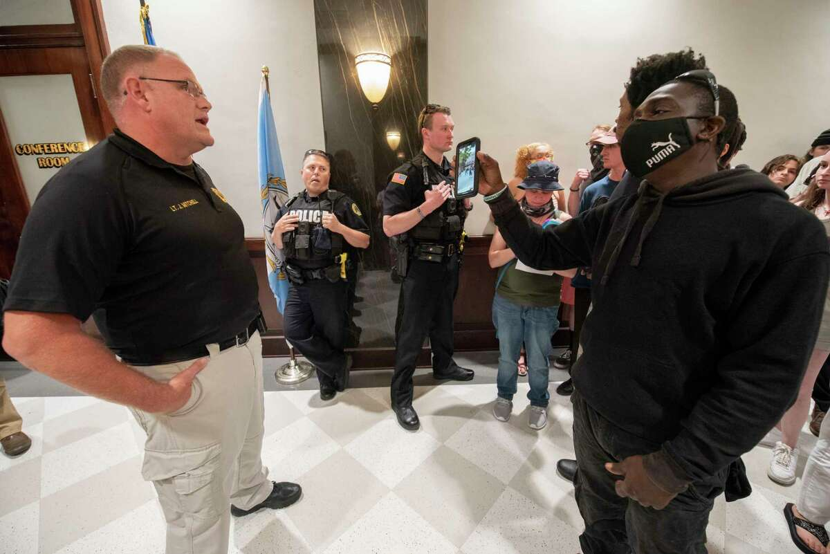Anthony Brown Davis, right, shows a video of the last protest where police showed up in riot gear to Lt. Jason Mitchell after Black Lives Matter demonstrators were kicked out of the council chambers at Saratoga City Hall on Tuesday, July 20, 2021 in Saratoga Springs, N.Y. (Lori Van Buren/Times Union)