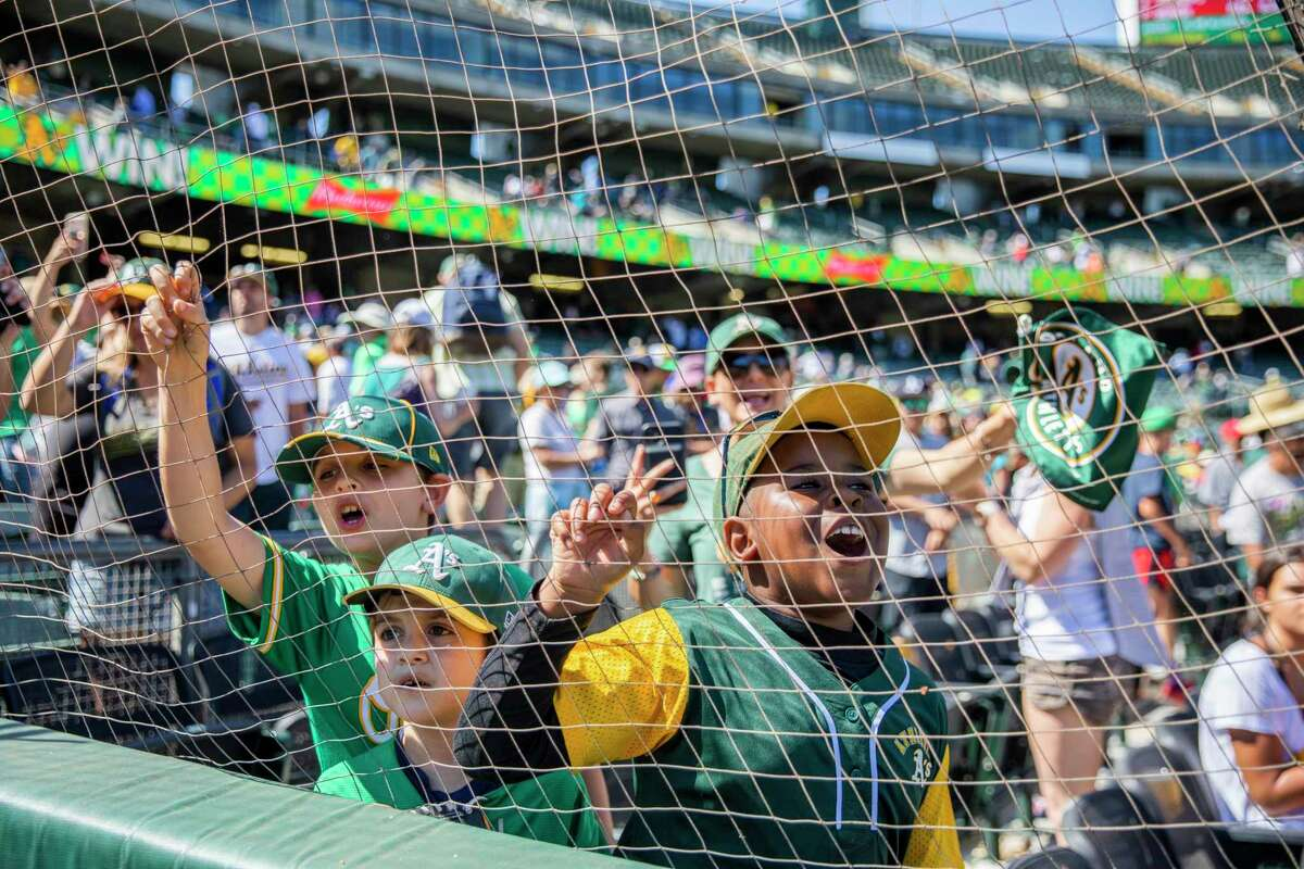 From left: Devon Fischer, 9, Dillon Fischer, 7, and Javaughn Thomas, 8, try to get the attention of Stomper, the Oakland Athletics' mascot following the MLB game between the A's and the Los Angeles Angels at RingCentral Coliseum on Tuesday, July 20, 2021, in Oakland, Calif. The A's won 6-0.