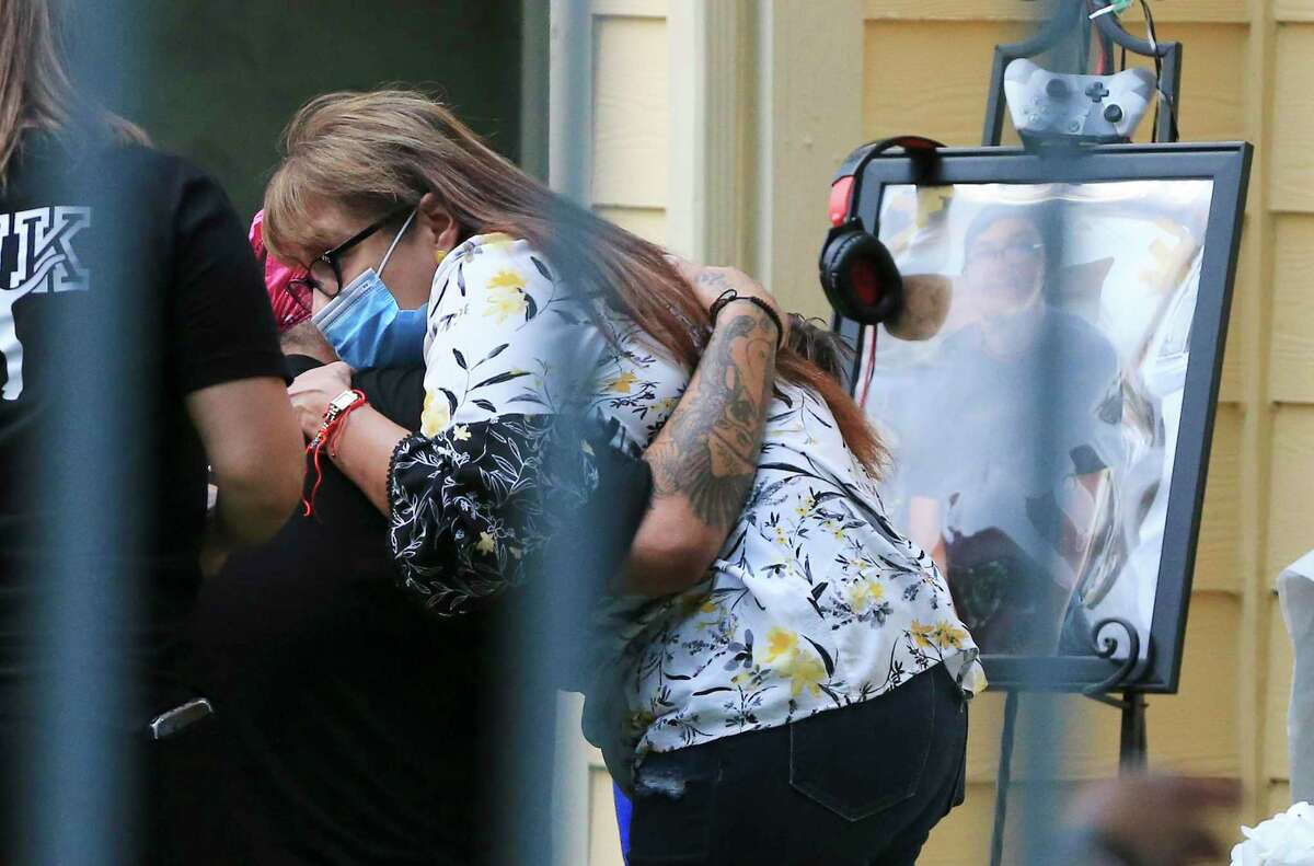 A mourner hugs Epi Rosas, the father of 15-year-old Tristian Jaden Rosas, who died early Tuesday, July 20, 2021, after he was hit by a stray bullet while inside his family's apartment. Family and friends held a private vigil at the apartment complex Tuesday evening.