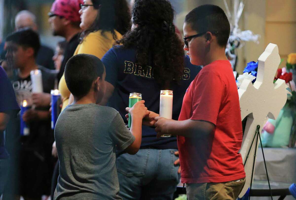 Two boys hold candles as mourners gather for a vigil to remember Tristian Jaden Rosas.