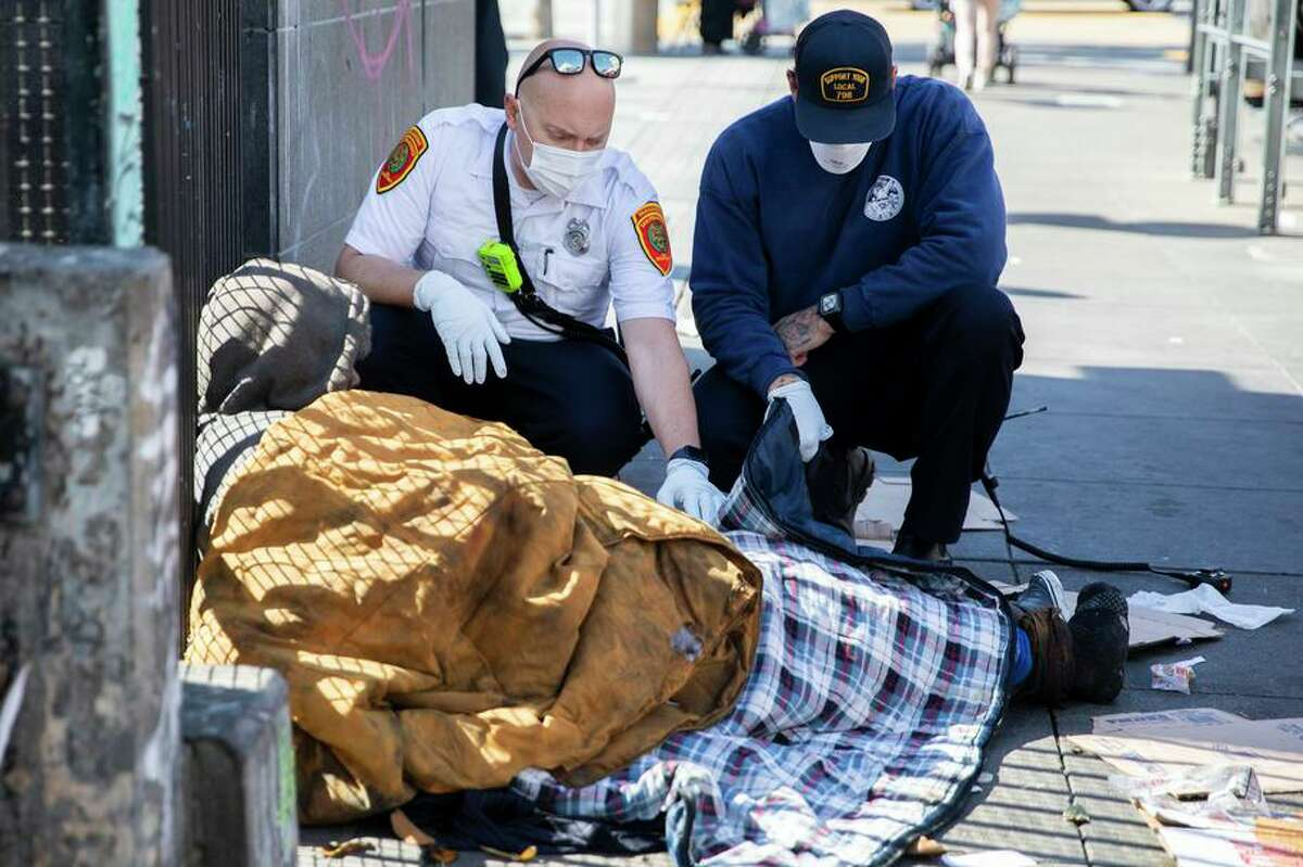 S.F. paramedic Eddy Bird (left) and EMT Brandon Backman talk with a homeless man in distress after receiving a 911 call.
