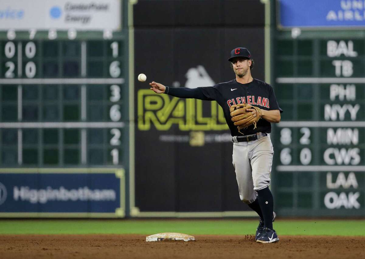 Cleveland shortstop Ernie Clement (28) turns a double play against the Houston Astros during the eighth inning of an MLB game at Minute Maid Park on Tuesday, July 20, 2021, in Houston.