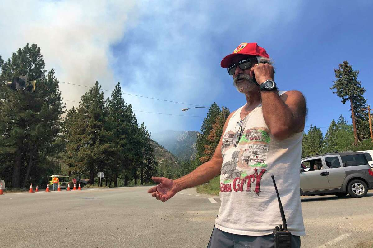 Tony Galvez, who lost his home to the Tamarack Fire, talks on his phone with his daughter in Vermont who's setting up a GoFundMe for him as he waved and clapped at passing firefighters in Woodfords, Calif., on Tuesday, July 20, 2021. In Northern California, authorities expanded evacuations for the Tamarack Fire in Alpine County in the Sierra Nevada to include the mountain town of Mesa Vista late Monday. That fire, which exploded over the weekend was 61 square miles with no containment.