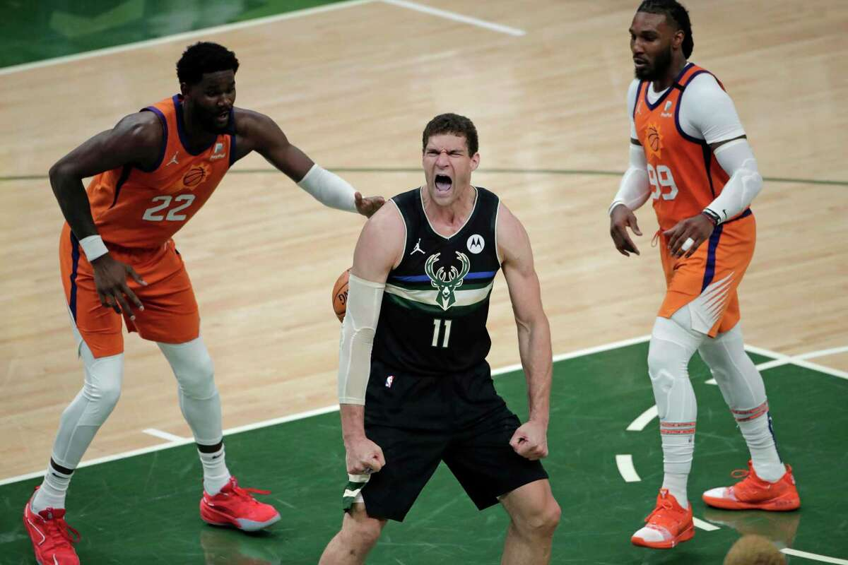 Milwaukee Bucks center Brook Lopez (11) reacts after a slam dunk in front of Phoenix Suns center Deandre Ayton (22) and forward Jae Crowder (99) during the second half of Game 6 of basketball's NBA Finals Tuesday, July 20, 2021, in Milwaukee. (AP Photo/Aaron Gash)