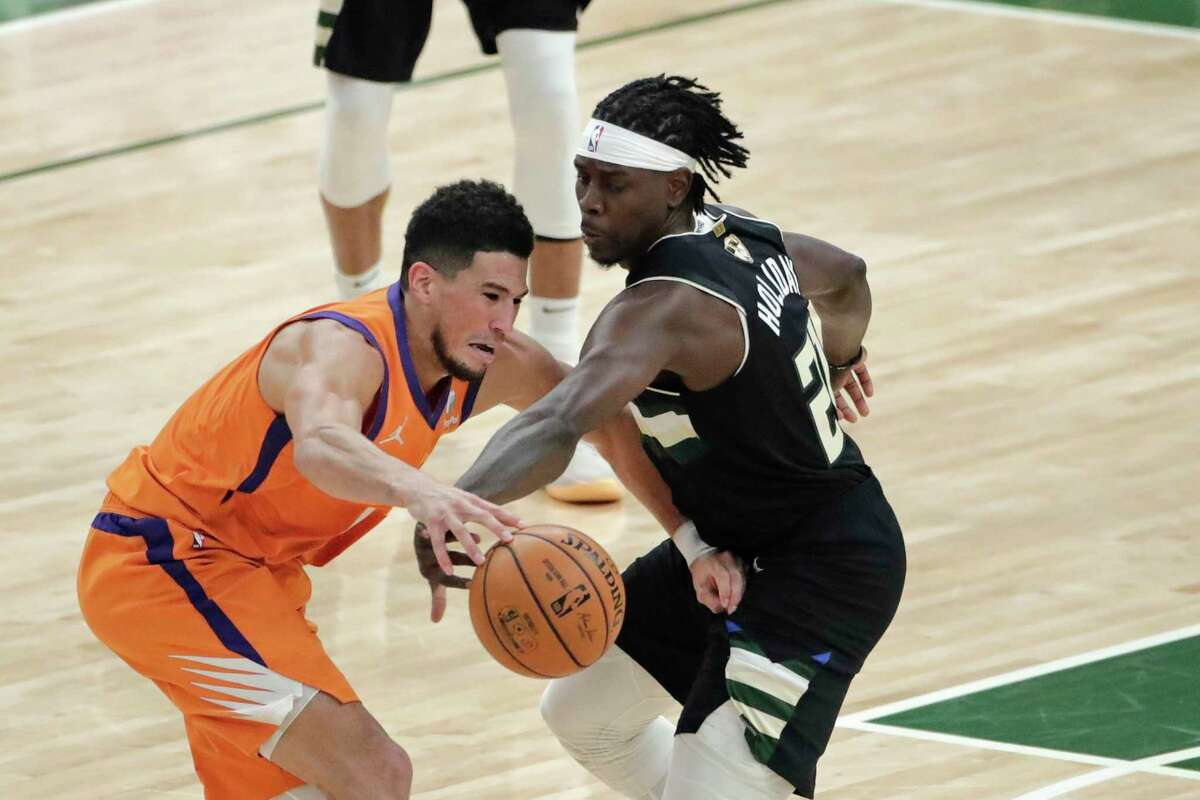 Phoenix Suns guard Devin Booker battles against Milwaukee Bucks guard Jrue Holiday, right, during the second half of Game 6 of basketball's NBA Finals Tuesday, July 20, 2021, in Milwaukee. (AP Photo/Aaron Gash)