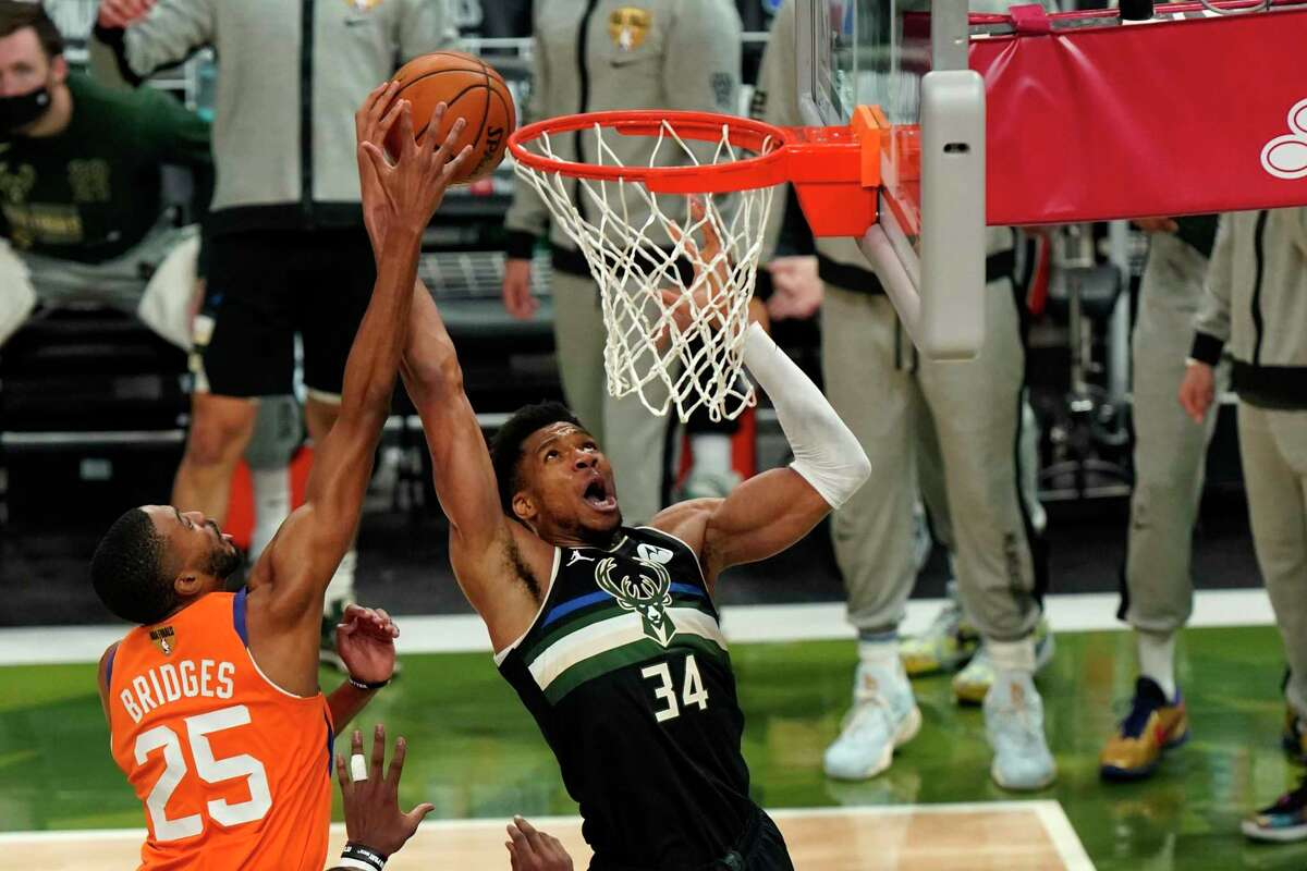 Milwaukee Bucks forward Giannis Antetokounmpo (34) goes to the basket against Phoenix Suns forward Mikal Bridges (25) during the second half of Game 6 of basketball's NBA Finals in Milwaukee, Tuesday, July 20, 2021. (AP Photo/Paul Sancya)
