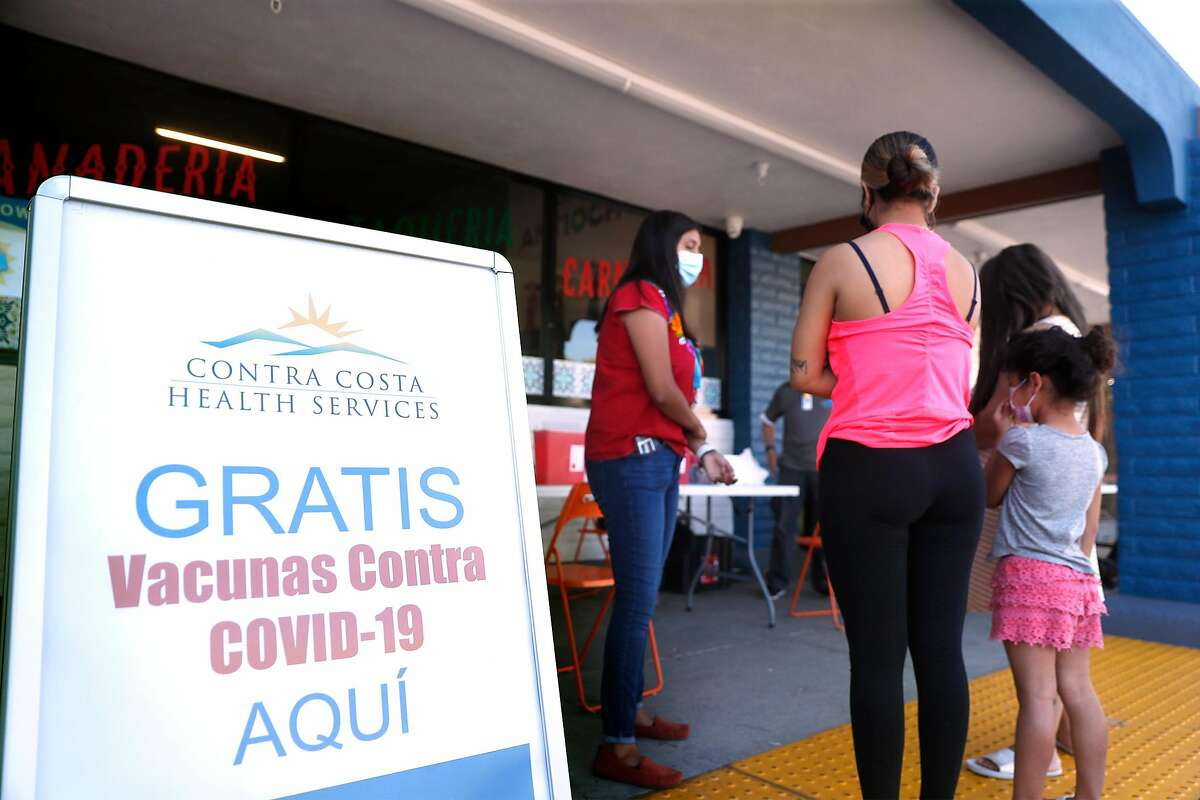 Contra Costra Health Services' community ambassador Shirley Canela talks to shoppers about getting their COVID vaccination at Cielo Market in Antioch, Calif., on Thursday, July 15, 2021. Antioch has some of the lowest vaccination rates in Contra Costa County and the Bay Area.