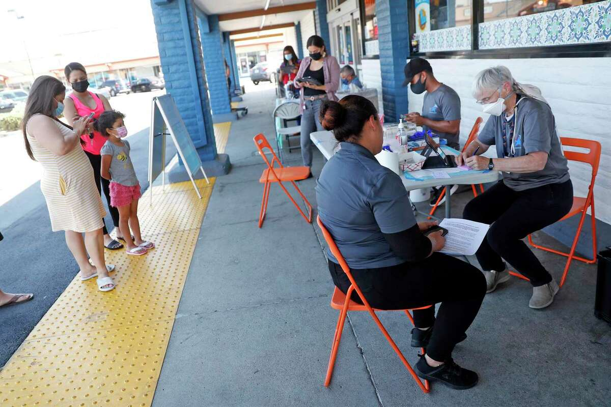 Contra Costra Health Services' physician Mary Clemency finishes up paperwork after administering a COVID vaccine to Cielo Market employee Seyla Machigua outside the market in Antioch, Calif., on Thursday, July 15, 2021. Antioch has some of the lowest vaccination rates in Contra Costa County and the Bay Area.