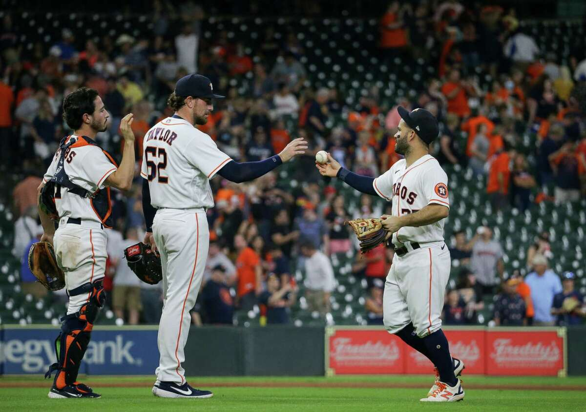 Houston Astros second baseman Jose Altuve (27), right, hands the ball that was the last out of an MLB game against Cleveland to relief pitcher Blake Taylor (62) at Minute Maid Park on Tuesday, July 20, 2021, in Houston.