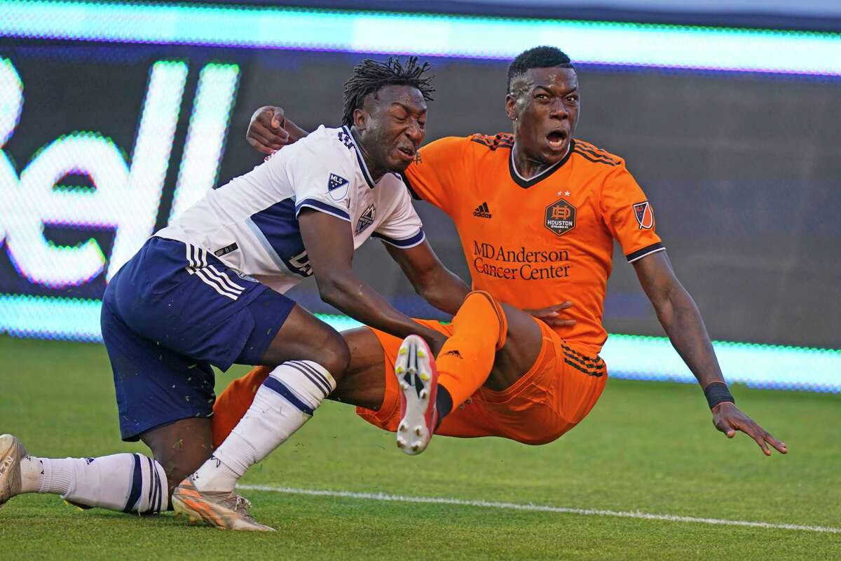 Teenage Hadebe (right) mades his Dynamo debut but his new team couldn't find any offense in a 0-0 tie against Vancover and Janio Bikel on Tuesday night in Sandy, Utah.