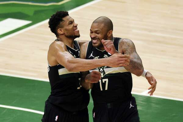MILWAUKEE, WISCONSIN - JULY 20: Giannis Antetokounmpo #34 of the Milwaukee Bucks celebrates with teammate P.J. Tucker #17 in the final seconds before defeating the Phoenix Suns in Game Six to win the 2021 NBA Finals at Fiserv Forum on July 20, 2021 in Milwaukee, Wisconsin. NOTE TO USER: User expressly acknowledges and agrees that, by downloading and or using this photograph, User is consenting to the terms and conditions of the Getty Images License Agreement.