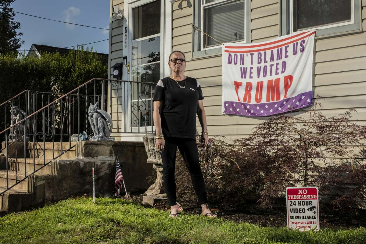 Andrea Dick outside her home, with one of the political signs a judge said she did not have to remove, in Roselle Park, N.J., July 19, 2021. When local officials asked her to take down several of the banners that they said violated an anti-obscenity ordinance, she refused. Now, she is resisting a judge's order that she do so and pledging to fight it in court on free speech grounds. (Bryan Anselm/The New York Times)