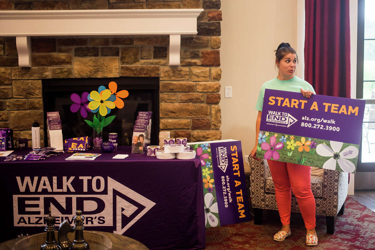 Abby Scherzer, event manager for the Alzheimer's Association Michigan Chapter, right, chats with guests during a kick off party Tuesday, July 20, 2021 for the Walk to End Alzheimer's, which is scheduled to take place Saturday, Oct. 9 at Dow Diamond. (Katy Kildee/kkildee@mdn.net)