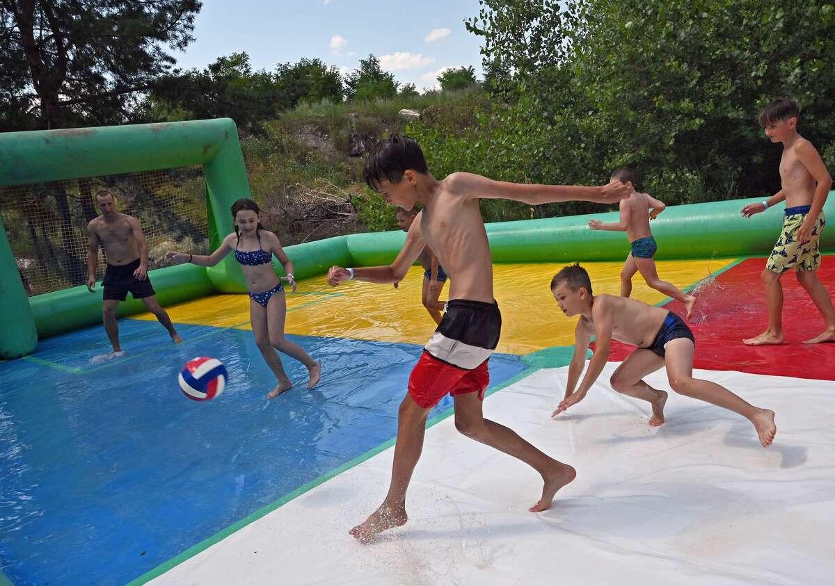 FILE - Children play football in a shallow swimming pool at a water park in summer, Sievierodonetsk, Luhansk Region, eastern Ukraine. (Photo credit should read Oleksii Kovalov/ Ukrinform/Barcroft Media via Getty Images)