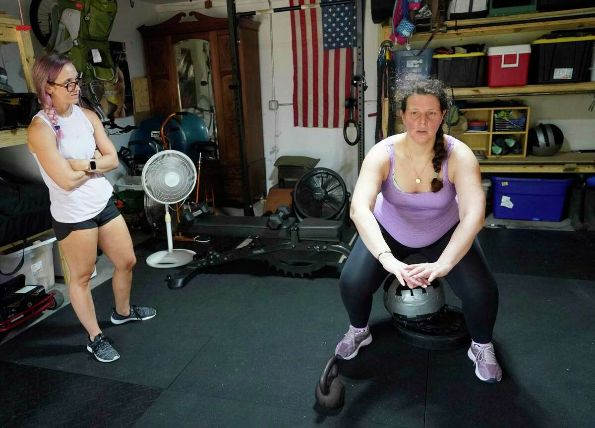 Cat Monzon, left, who is certified as a prenatal and postpartum trainer, works with client Jeni Masi Saturday, July 17, 2021 in Houston. Jeni knew she needed extra help from someone who knew how to modify workouts for pregnancy.