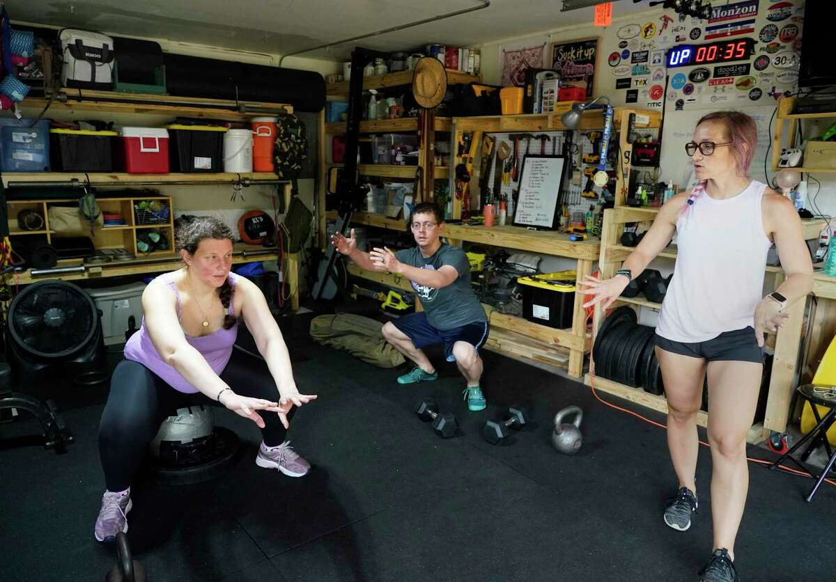 Jeni Masi, left, along with her husband, Jon Flynn, center, work out with Cat Monzon, who is certified as a prenatal and postpartum trainer, Saturday, July 17, 2021 in Houston. Jeni knew she needed extra help from someone who knew how to modify workouts for pregnancy.