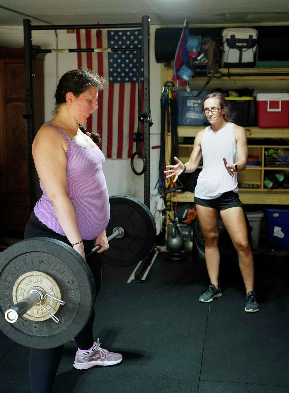 Jeni Masi, left, works out with Cat Monzon, who is certified as a prenatal and postpartum trainer, Saturday, July 17, 2021 in Houston. Jeni knew she needed extra help from someone who knew how to modify workouts for pregnancy.