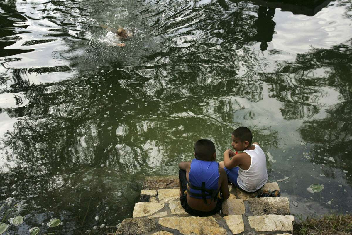 In this 2005 photo, San Antonio Housing Authority residents Michael Jimenez, 7, left, and Eddie Gonzales, 8, watch fellow campers slide into the Guadalupe River at YMCA Camp Flaming Arrow in Hunt. Open since 1927, the camp is closing this year.