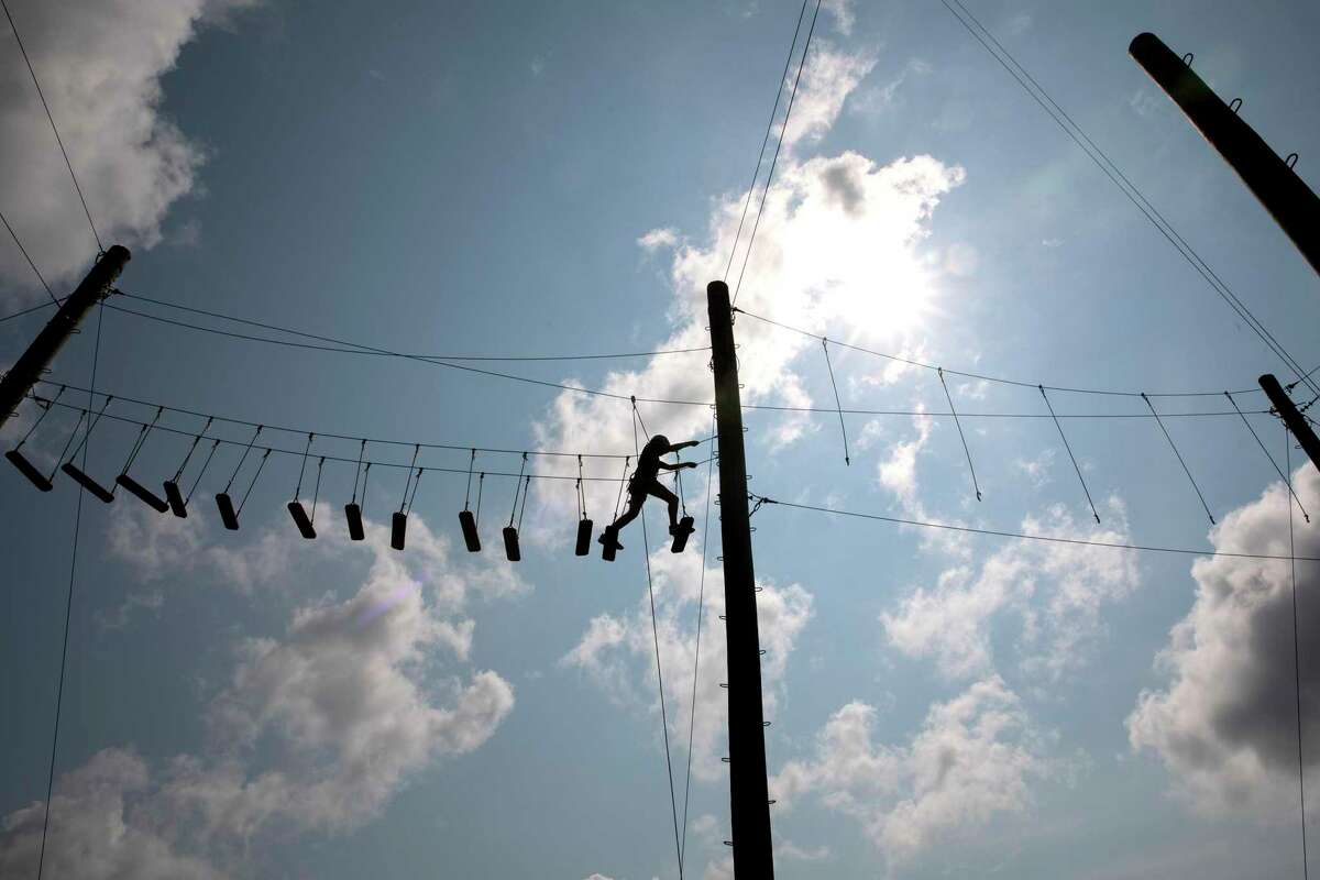 """Lucienne """"Dove"""" Brown, 11, walks through the high ropes course at YMCA Camp Flaming Arrow."""