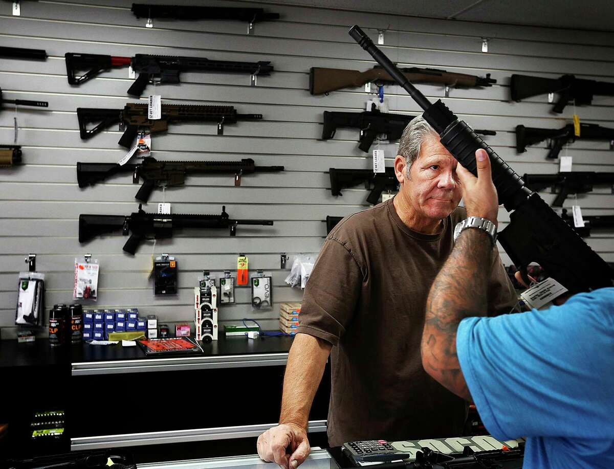Gunsmith, Frank Cobet, of the Get Loaded gun store in Chino, Calif., shows a customer an AR-15 rifle on Tuesday, Dec. 8, 2015. The FBI struggles to complete hundreds of gun background checks each year because of a deadline that requires it to purge them from its computers, according to data. (Barbara Davidson/Los Angeles Times/TNS)
