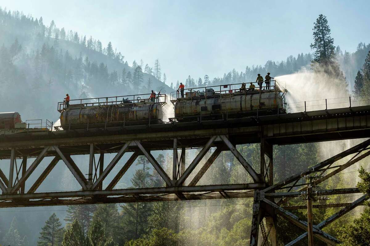 Firefighters spray water from Union Pacific Railroad's fire train while battling the Dixie Fire in Plumas National Forest, Calif., on Friday, July 16, 2021.