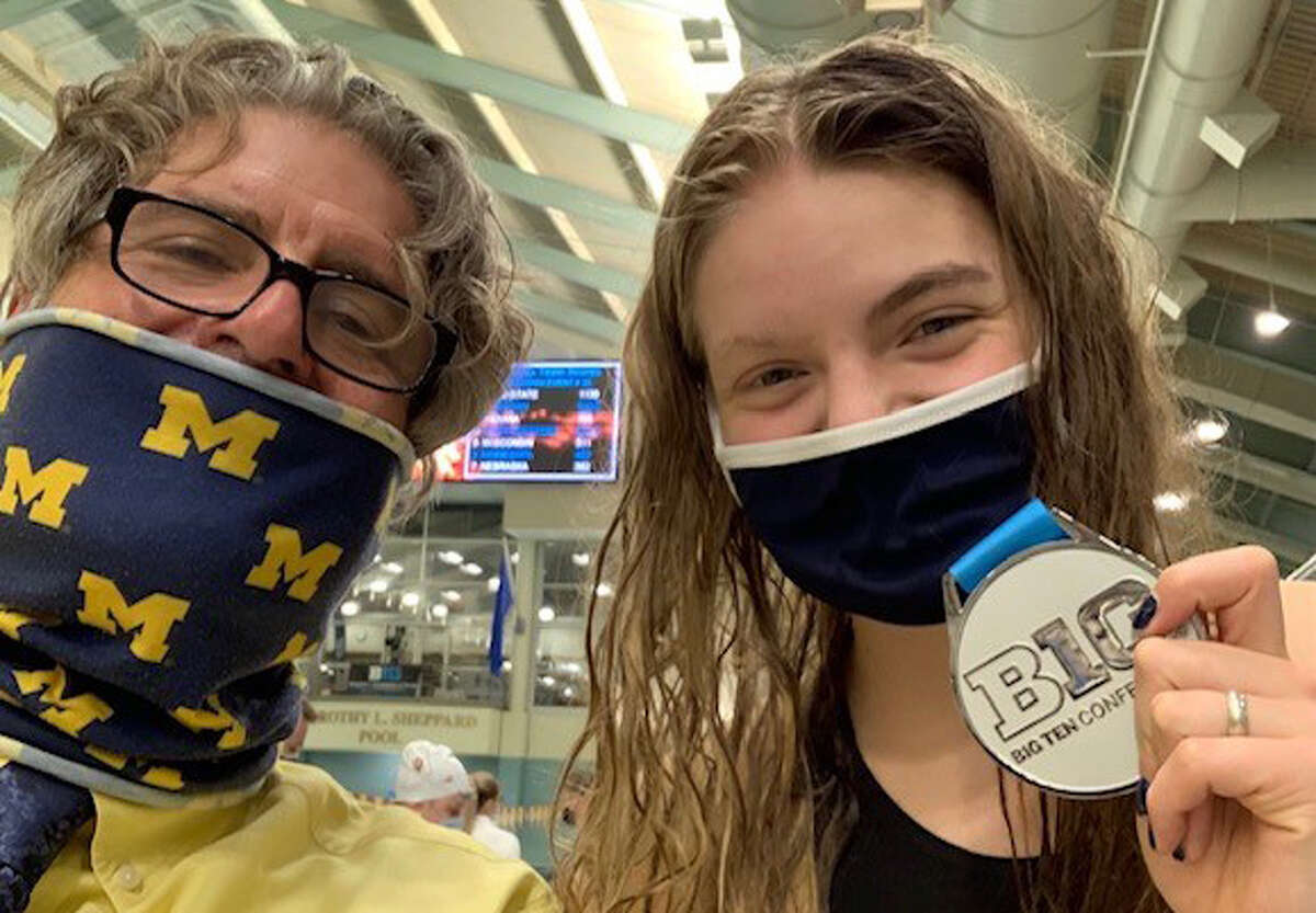 Dow High alum Claire Newman poses alongside University of Michigan women's swimming coach Mike Bottom with the medal she earned as part of the Wolverines' second-place 200-yard freestyle relay team at the 2021 Big Ten Championships this past spring.