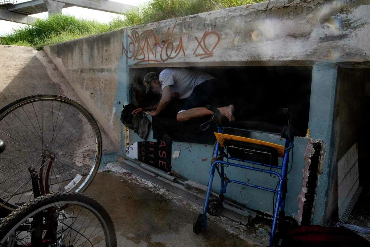 Mike Stevens climbs over a makeshift wall and into a drainage tunnel where he has made his home. Stevens lost all his possessions during a recent heavy rain. Luckily, he was not in the tunnel during the storm.