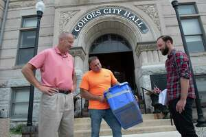 Cohoes Mayor Bill Keeler, left, stands Steve Hennessy, commissioner of Public Works, center, and City Planner Joe Seman-Graves at Cohoes City Hall on Wednesday, July 21, 2021 in Cohoes, N.Y.  The mayor was discussing the new initiative of an attempt to increase recycling with 4,500 new recycling carts replacing the current bins like the one Hennessy is holding. (Lori Van Buren/Times Union)