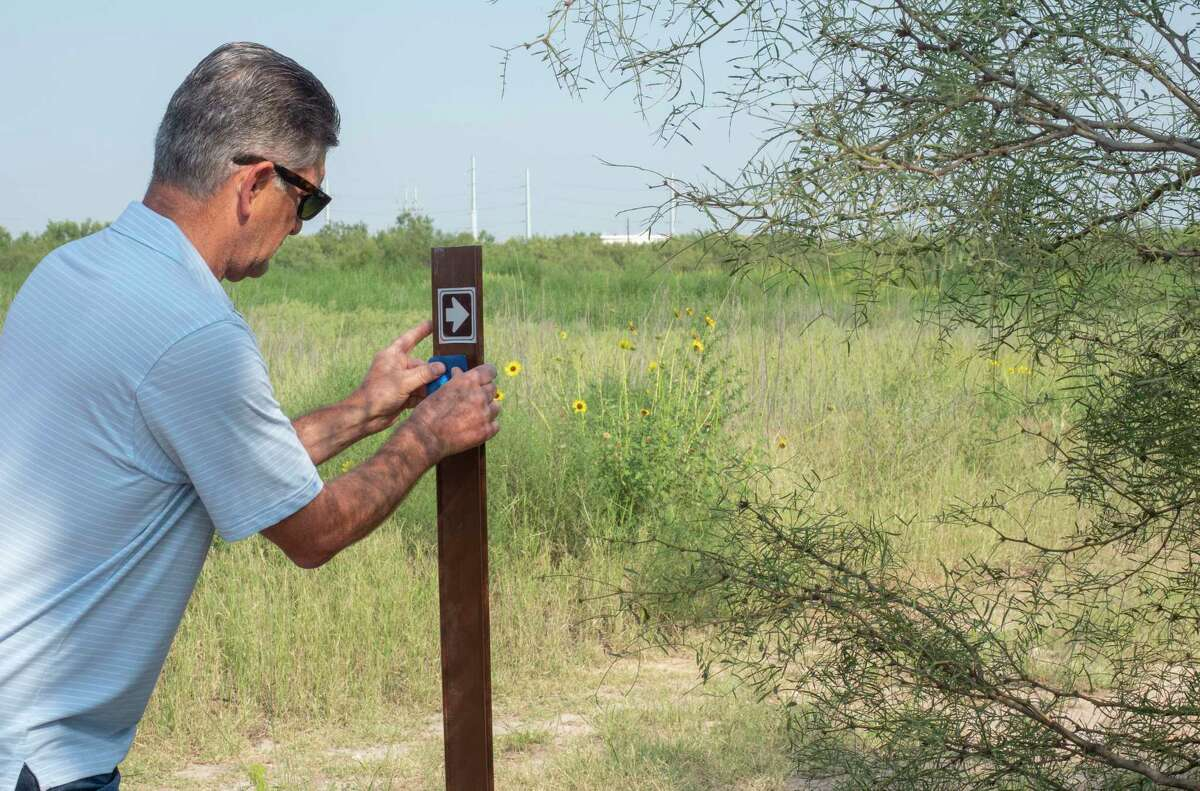 Stephen Mitchell, mountain bike director for Permian Basin Bicycle Association, places a blue marker on a trail head marker as he leads city council members Lori Blong and Jack Ladd 07/21/2021 at the new mountain bike trail area off Hwy 307. Tim Fischer/Reporter-Telegram
