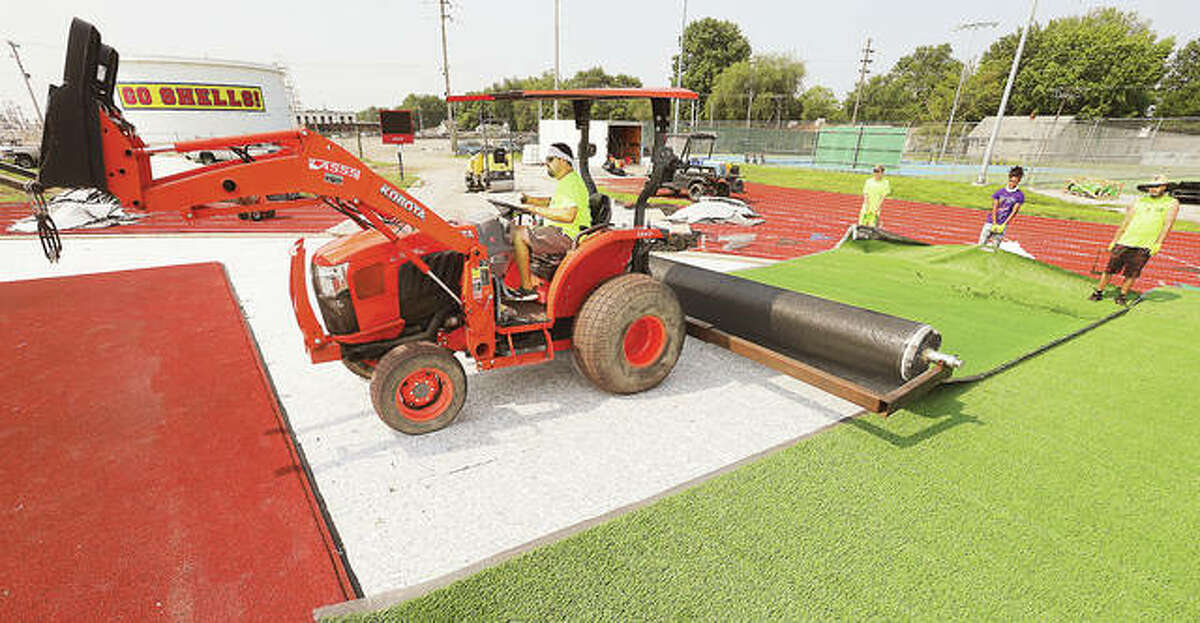 A tractor unrolls another strip of artificial turf Wednesday at the Charles Raich Football Field at Roxana High School. Work is nearing the final stages on the football field, but prep work is still underway at the nearby soccer field which will also have artificial turf.