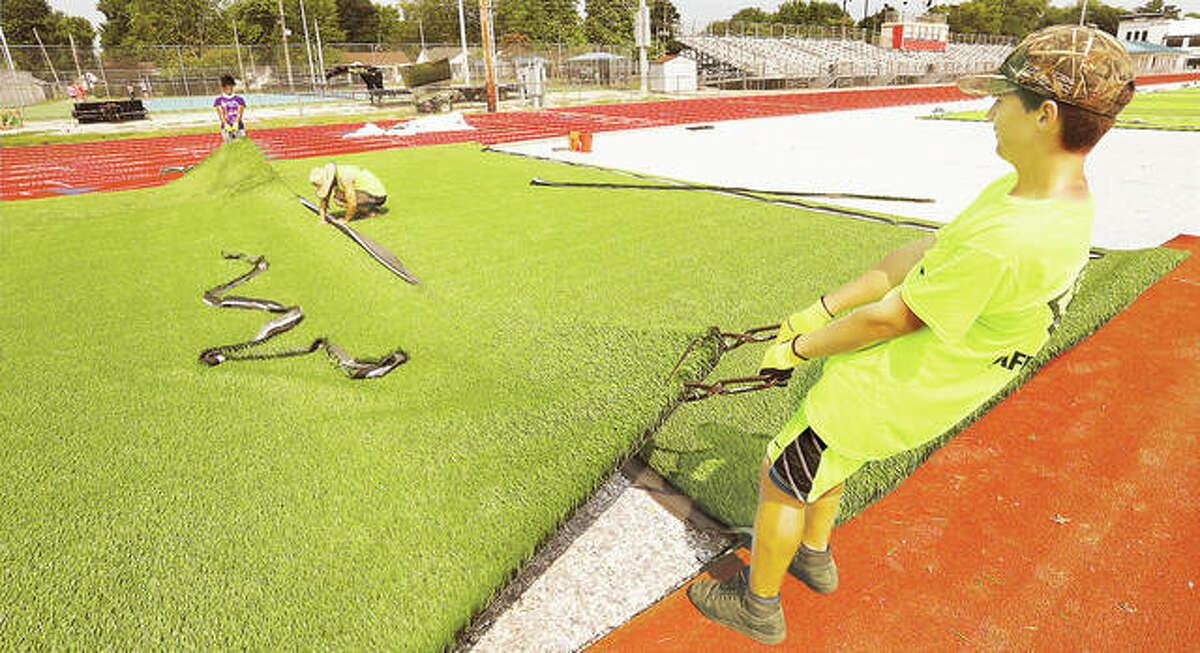 Two workers pull a new section of turf to line up the seams.