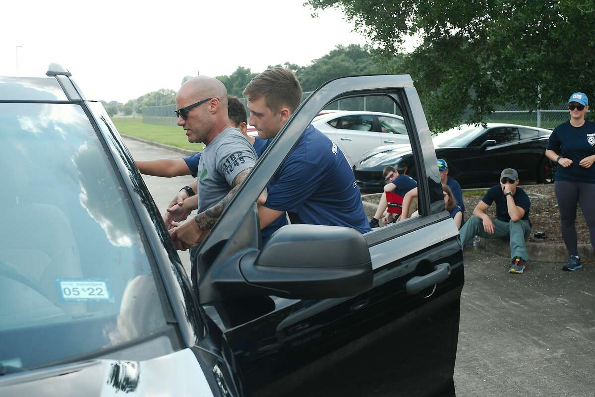 Montero poses as a driver as cadets Mason Bourda and Patrick Browne participate in frisk scenario during a mock traffic stop.