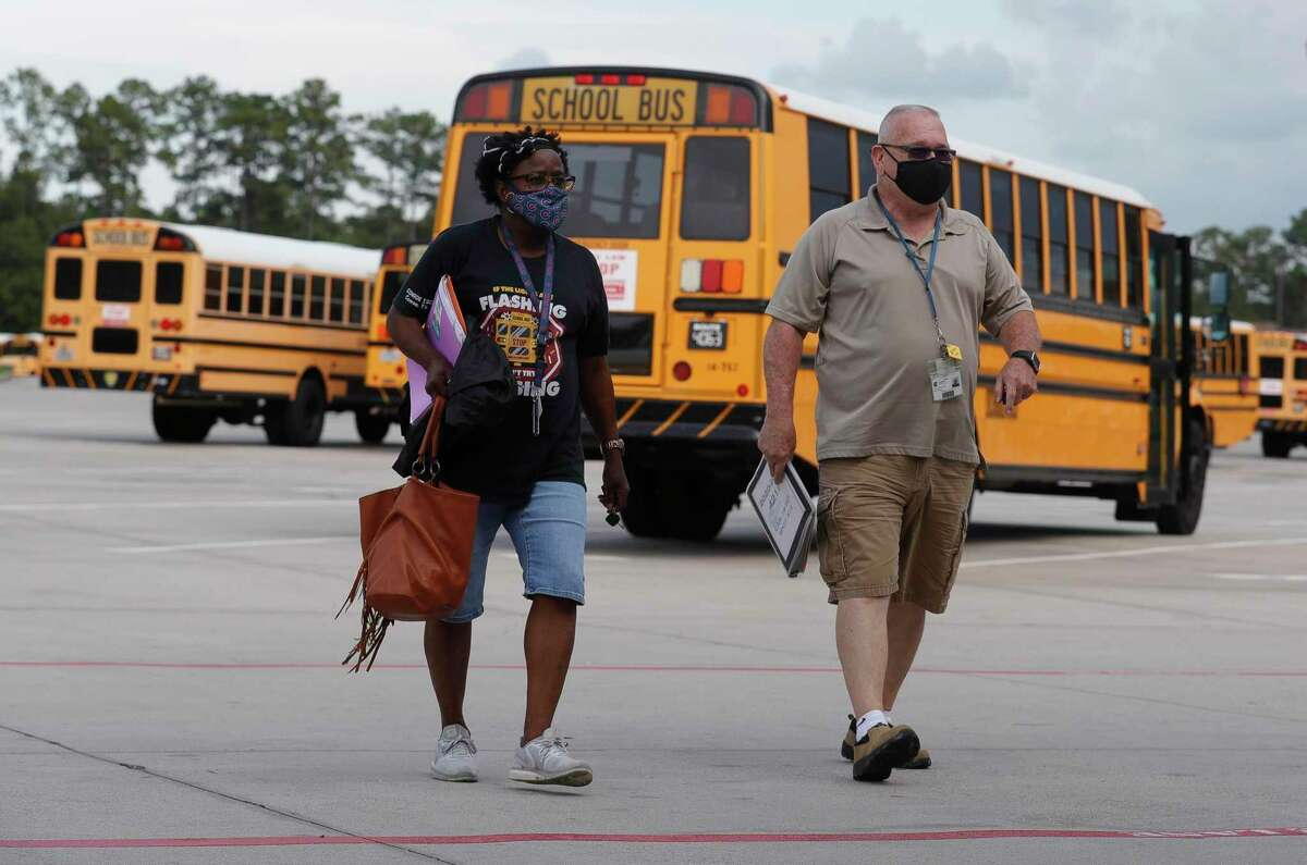 Bus drivers Gary Laporde, right, and Hattie Williams wear face masks as they head back to the main building after dropping off students Sept. 9, 2020, in Oak Ridge. Conroe ISD students are set to return to class on Aug. 11. But as students return, the strict COVID-19 mandates of last year will not, and the district won't be able to mandate that students positive with COVID-19 stay home to isolate.