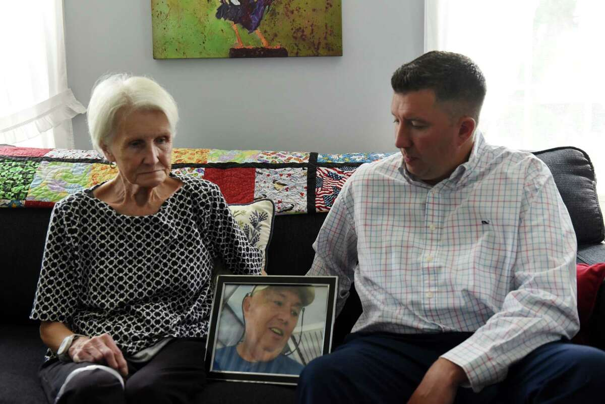 Michael Hickey, right sits beside his mother, Sue, with a photo of his later father, John, on Wednesday, July 21, 2021, at his mother?•s home in Hoosick Falls, N.Y. His father, who worked at the nearby Saint-Gobain factory for 32 years, died at 68 from kidney cancer. It was his death that prompted Michael to begin investigating why the village seemed to have a high rate of unusual cancer cases. Hickey blew the whistle on Hoosick Falls PFOA water contamination in 2015.