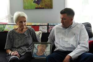 Michael Hickey, right sits beside his mother, Sue, with a photo of his later father, John, on Wednesday, July 21, 2021, at his motherÕs home in Hoosick Falls, N.Y. His father, who worked at the nearby Saint-Gobain factory for 32 years, died at 68 from kidney cancer. It was his death that prompted Michael to begin investigating why the village seemed to have a high rate of unusual cancer cases. Hickey blew the whistle on Hoosick Falls PFOA water contamination in 2015.