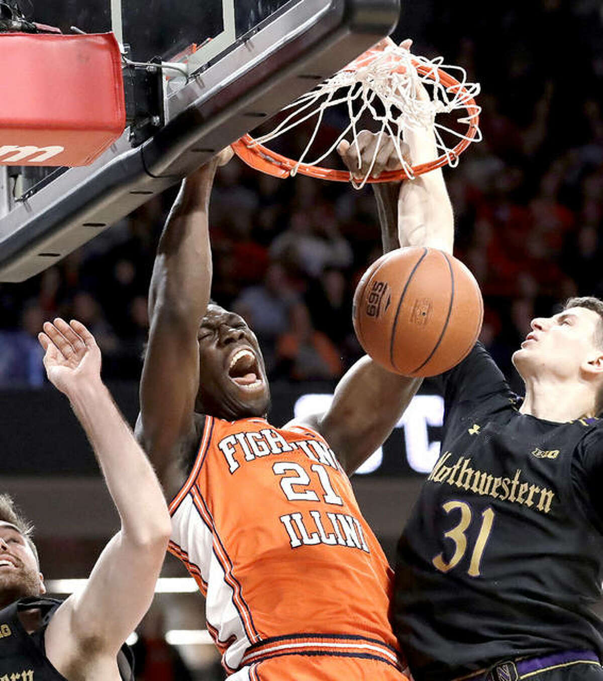 Illinois center Kofi Cockburn, center, dunks against Northwestern in 2020. Cockburn, who had entered the transfer portal and declared for the NBA Draft, last week decided instead to return to Illinois this season. Wednesday was his first day to work out with the team.