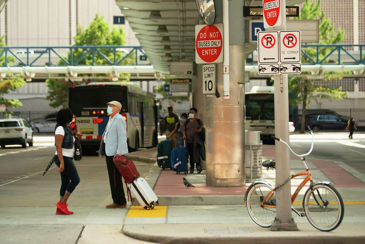Passengers navigate outside Metropolitan Transit Authority's downtown transit center on July 20, 2021, in downtown Houston. Metro's 1,200-bus fleet currently has zero electric vehicles.