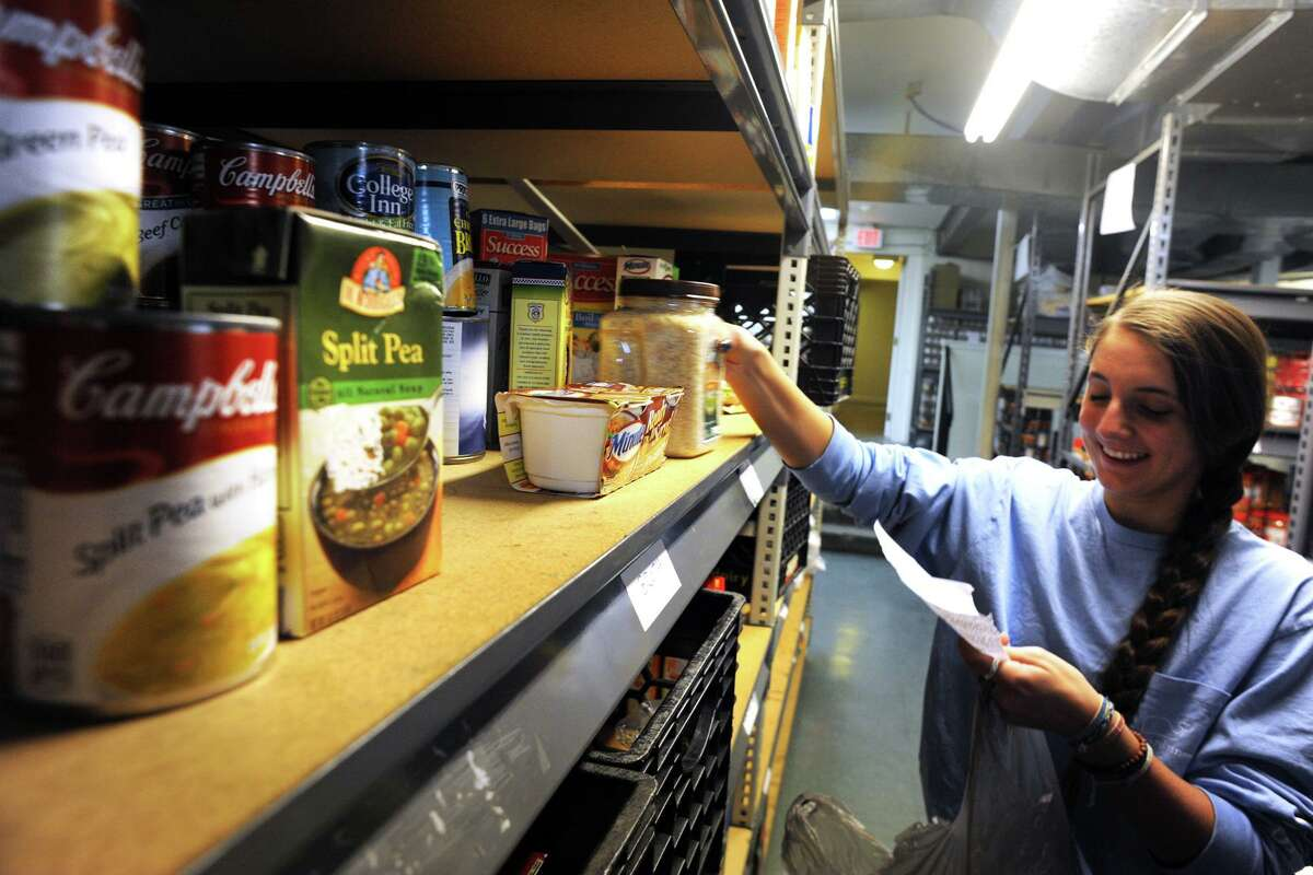 A volunteer fills an order for a customer during a busy afternoon at the Operation Hope Food Pantry, in Fairfield, Conn. Nov. 13, 2014.