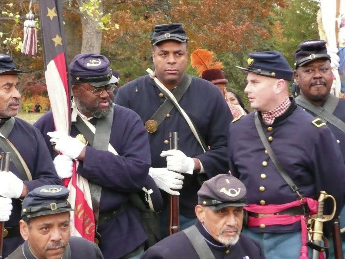 Calvin Osborne, center, president of the Black Civil War reenactment group 54th Massachusetts Volunteer Infantry Regiment, Company B, with other Civil War reenactors in 2014.