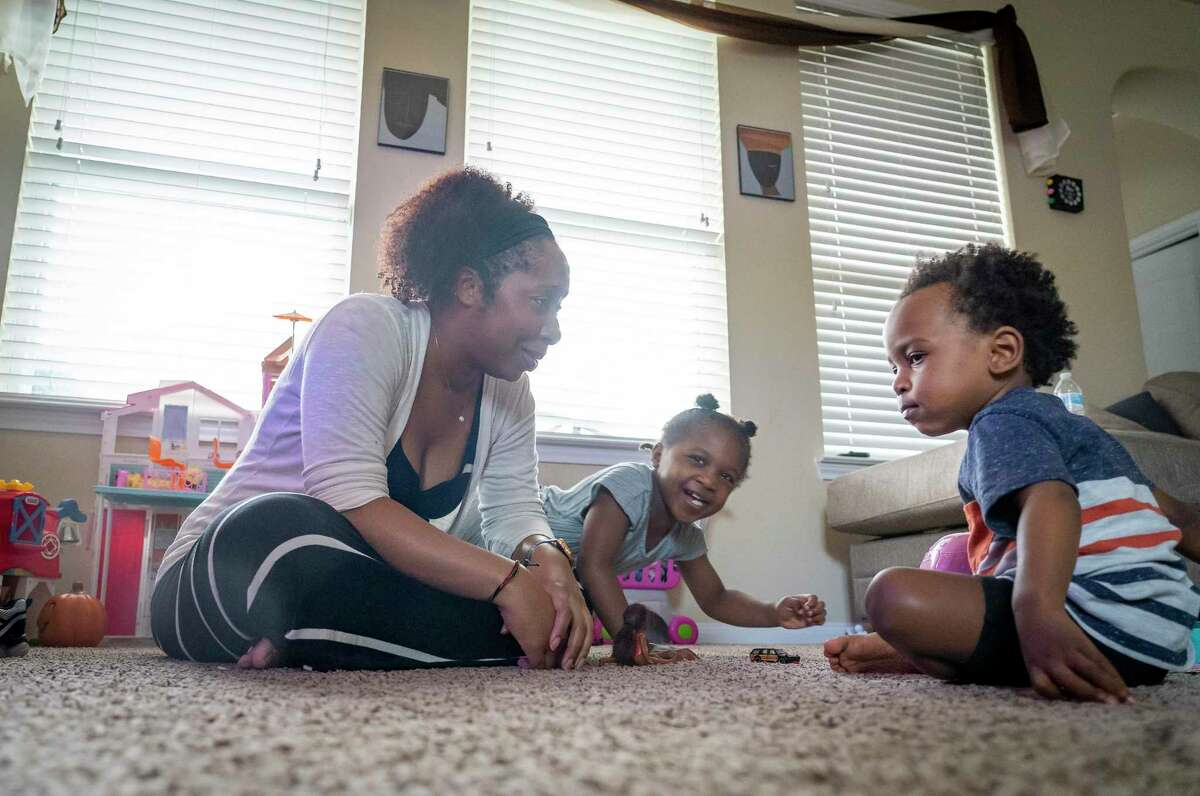 LaToya Washington, a high school teacher who heads back to work in the coming weeks, plays with her children, Jazilyn, 4, and Brysen, 2, in their living room, Wednesday, July 21, 2021, in Baytown. Washington received the Johnson & Johnson vaccine in March and is now researching the possibility of a booster if the vaccine doesn't seem to protect against the Delta variant of Covid-19.