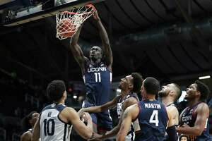 Connecticut forward Akok Akok (11) dunks against Butler during the first half of an NCAA college basketball game Saturday, Jan. 9, 2021, in Indianapolis. (Jenna Watson/The Indianapolis Star via AP)