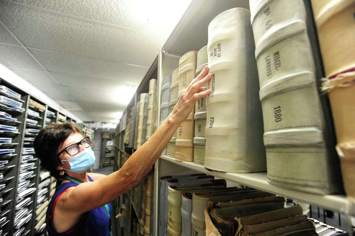 Stamford town clerk Lyda Ruijter pulls a book of records that are kept in storage at the Stamford Government Center on July 17, 2020.