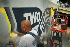 Graphics are painted on the exterior of the Two Roads Tap Room as the new Hartford Healthcare Amphitheater, a conversion of the former Harbor Yard Ballpark, prepares for July 28 opening night in Bridgeport Conn. on Wednesday, July 21, 2021.